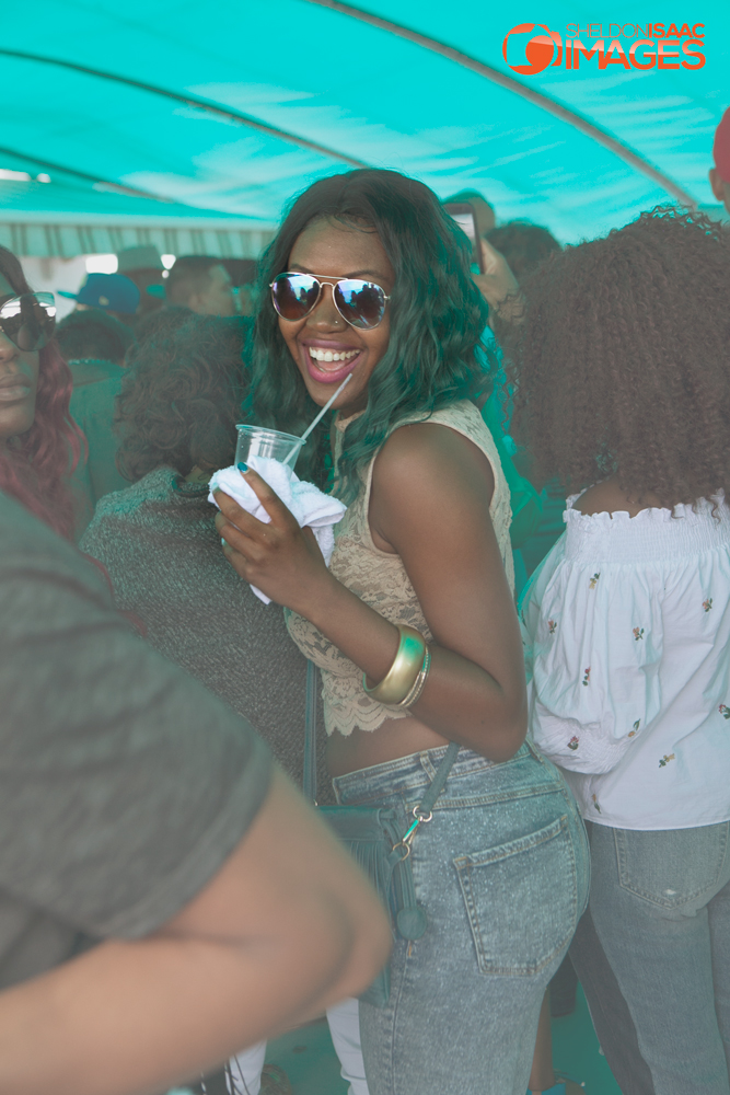 Lady parties with a cold drink on the Caribana Friends Boat Cruise