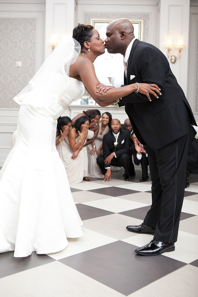 Ajax Wedding Photographer Sheldon Isaac Images photographs the Bride and Groom kissing with Bridal Party laughing