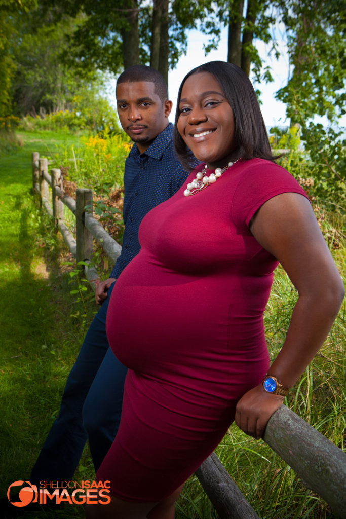 Pregnancy photo of wife and husband looking at camera