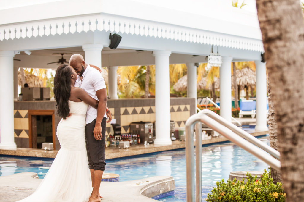 Bride and Groom hugging by the pool bar