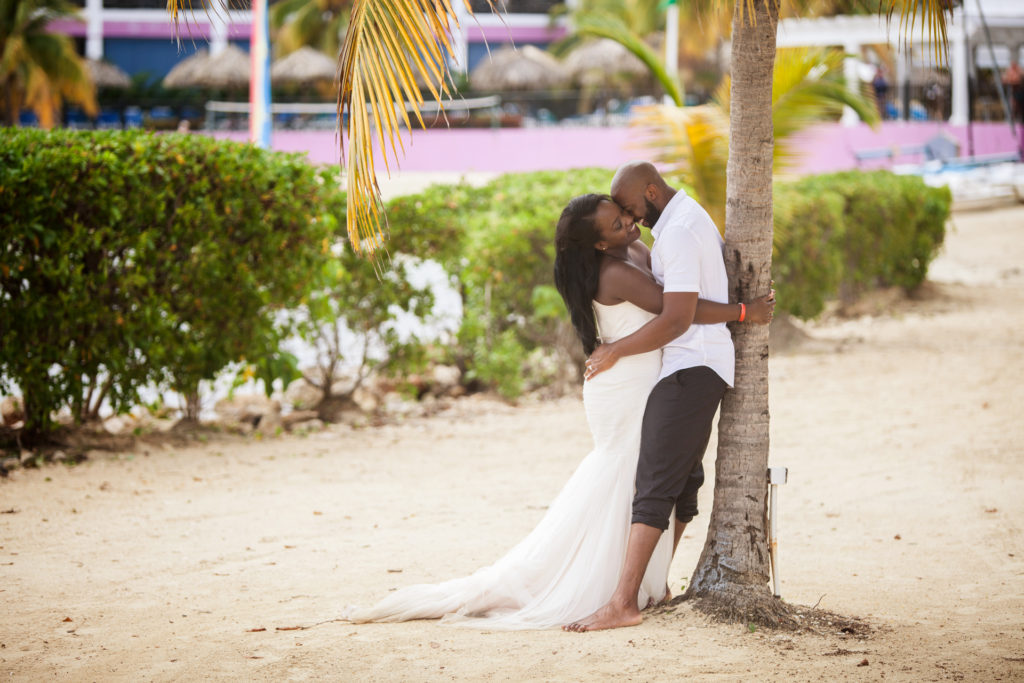 Groom kissing Bride under the palm tree in Jamaica